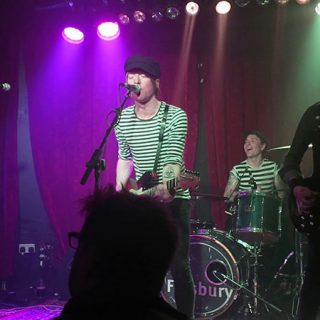 Foto de The Speedways tocando en directo en la que se ve a sus cuatro componentes con Matt Julian, el cantante, en el centro.