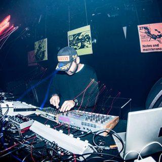 Foto de Voiski manejando la mesa de mezclas en una de sus sesiones en directo en un local oscuro.