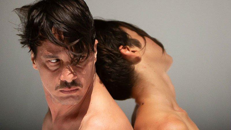 """Foto de una escena d la obra """"Anarquismos"""" en la que se ve a dos de sus protagonistas espalda con espalda desnudos."""