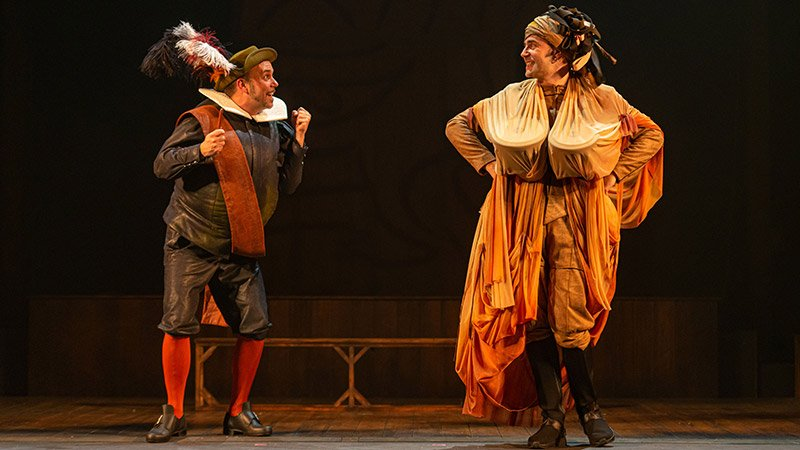 """Foto de una escena de la obra teatral """"Andanzas y entremeses de Juan Rana"""" en la que se ve a sus dos protagonistas en el centro del escenario mirándose con gesto burlesco."""