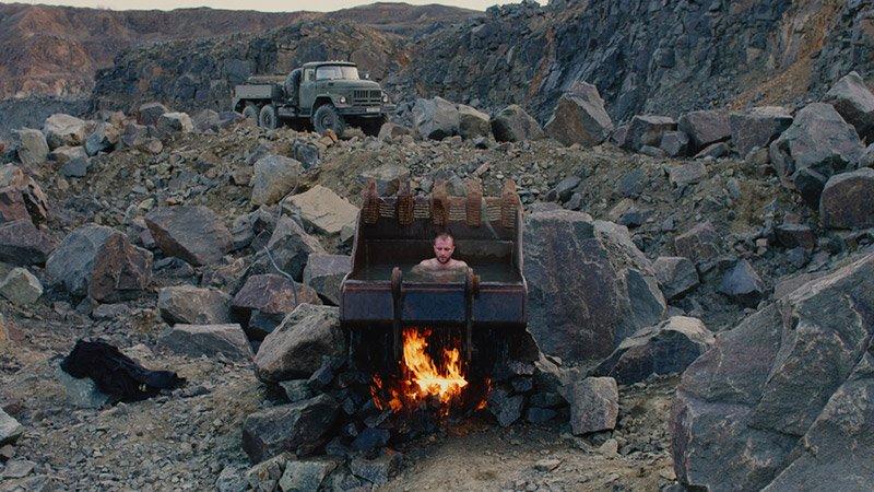 Fotograma de la película Atlantis en el que se ve u na paisaje denostado, un camión militar al fondo y a un hombre metido en la pala de una escavadora que le sirve de bañera.