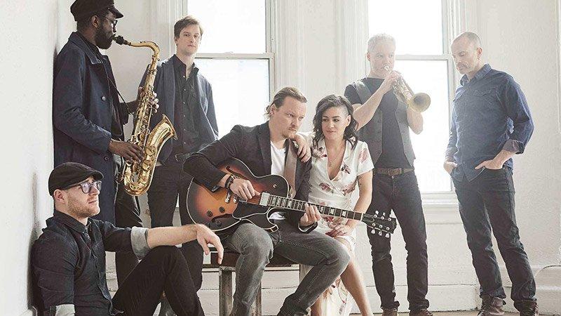 Foto de los siete componentes de Bywater Call dispuestos irregularmente en una habitación blanca con dos ventanas tras de sí, en el centro puede verse al guitarrista y la cantante sentados en una silla.
