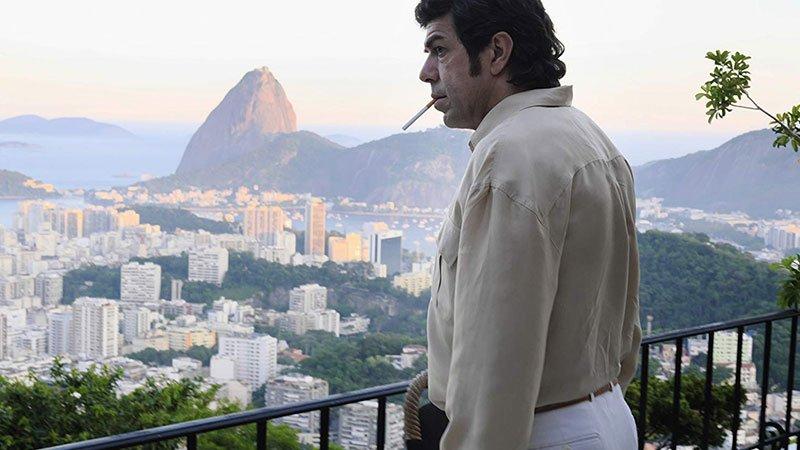 """Fotograma de la película """"Il traditore"""" en el que se ve a su protagonista asomándose a un balcón con una gran vista delante mientras sostiene un cigarrillo en la boca."""