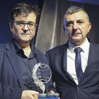 Fotografía de los escritores Javier Cercas y Manuel Villas sosteniendo el premio Planeta.