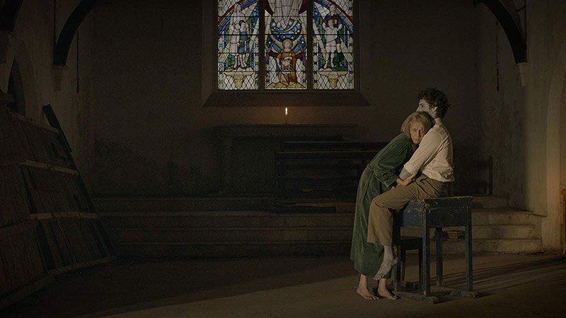 Fotograma de la película Jonaki en la que se ve el altar de una iglesia en el que una mujer abraza a un chico con color de cadáver que está sentado sobre una mesa.