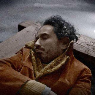 """Fotograma de la película """"Longa Noite"""" en el que se ve a su protagonista durmiendo en una barca obre un río."""