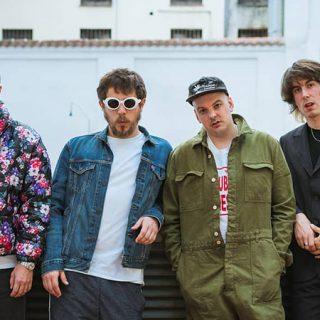 Foto de los cuatro integrantes de Novedades Carminha posando antes u n muro con cara de pasmaos.
