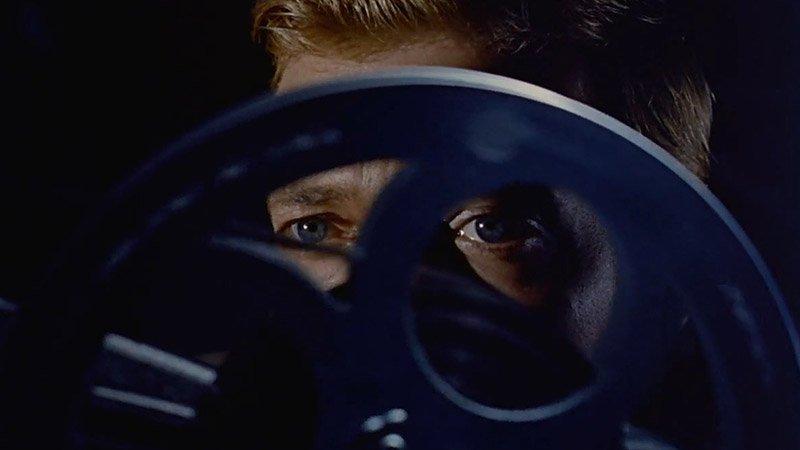 """Fotograma de la película """"Peeping Tom"""" en el que se ve a su protagonista mirando a través de los agujeros de un rollo de película."""