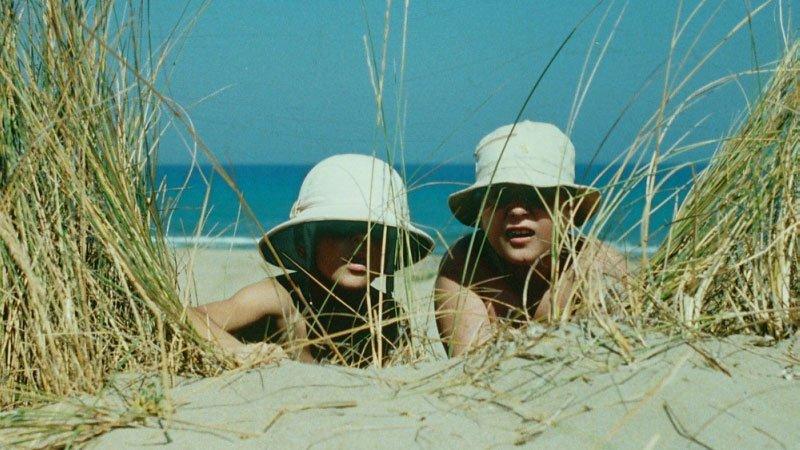 Fotograma de la película Peppermint en el que se e a dos niños escondidos tras una duna en una playa, con el mar al fondo y unos juncos que les esconden de algo a lo que miran con curiosidad.