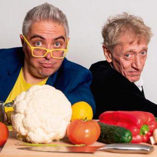 Foto de los dos protagonistas de Pesadilla en la Comedia posando ante una mesa llena de verduras y utensilios de cocina.