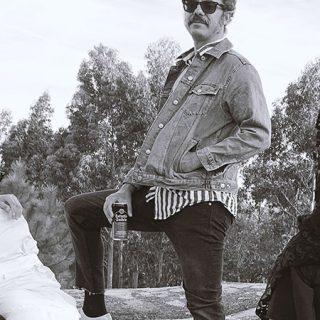 Foto en blanco y negro de los tres componentes de Rata Negra mirando a cámara, con unas latas de cerveza en la mano mientras uno de ellos abraza a una especie de momia casera y la cantate se oculta tras un velo rollo saeta.
