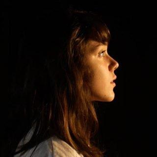 """Fotograma del cortometraje """"Revelación"""" en le que se ve a una niña de perfil observando algo con gesto de asombro."""