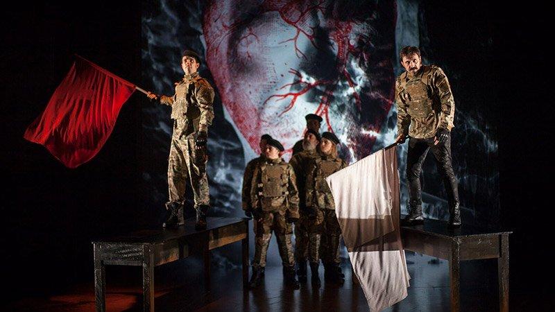 Foto de una escena de la obra Ricardo III en la que se ve a un grupo de soldados al fondo, en el primer plano otros dos soldados sostienen una bandera roja y otra blanca respectivamente.