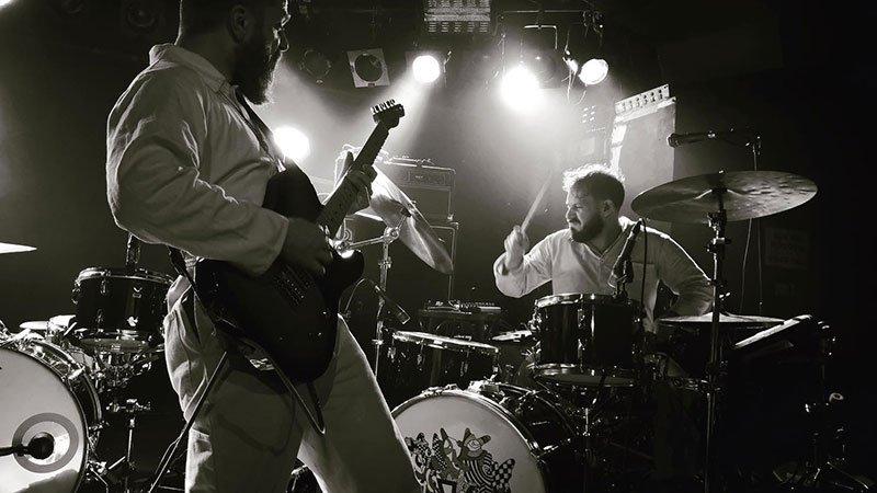 Foto de los dos componentes de Rival Karma tocando en directo y mostrando toda su fuerza a la guitarra y batería.