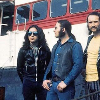 """Fotograma del documental """"Romantic Warriors IV: Krautrock"""" en el que se ve a cuatro músicos de krautrock de pie ante un barco."""