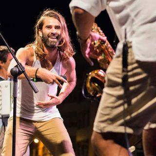 Foto de Rupatrupa tocando en directo donde se ve a Roberto Ruido en el centro sonriendo y haciendo gestos al saxofonista, que aparece d espaldas en la derecha del plano muy cerca de la cámara.