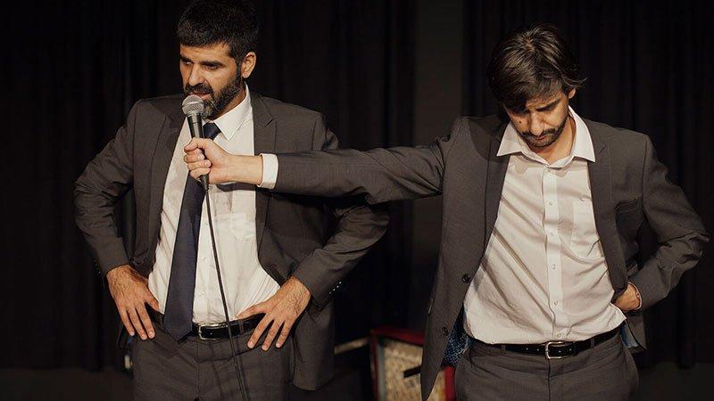 """Foto de una escena de la obra """"Sueños y visiones de Rodrigo Rato"""" en la que se ve a sus dos protagonistas de pie, uno junto al otro, ambos vestidos de traje. El de la derecha extiende la mano con un micrófono para ponerlo junto a la boca del otro."""