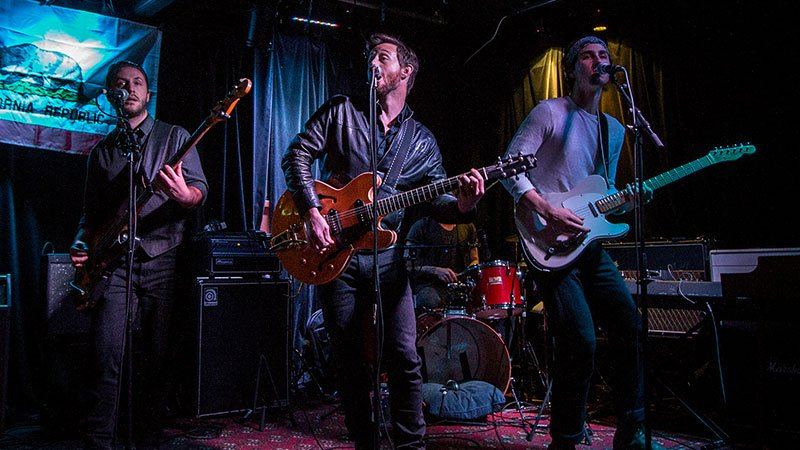 Foto de los cuatro componentes de Kingsborough tocando en directo en un pequeño escenario muy americano.