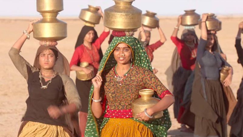 Fotograma de la película Hellaro en el que se ve a un grupo de mujeres camninado por el desierto con ropas muy coloridas sosteniendo vasijas doradas en sus cabezas.