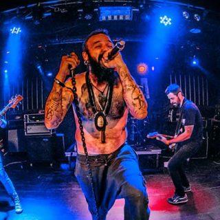 Foto de Bocanada en directo donde se ve en primer plano y en el centro de la imagen al cantante sin camiseta con gesto enérgico mientras agarra el micro con fuerza, detrás puede verse al guitarrista y el bajista tocando con ahínco.