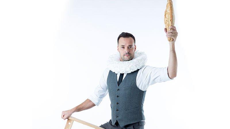 Foto promociona de la obra de teatro Hambre en la que se ve a su protagonista alzando una barra de pan.