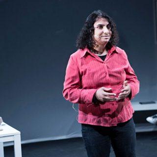 """Foto de una escena de la obra de teatro documental """"Nadia"""" en la que se ve a su protagonista e pie en el centro de la escena."""