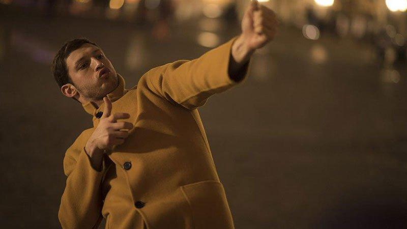 Fotograma de la película Synonymes en el que se ve a su protagonista en la calle haciendo un gesto con las manos como si disparase un arma.